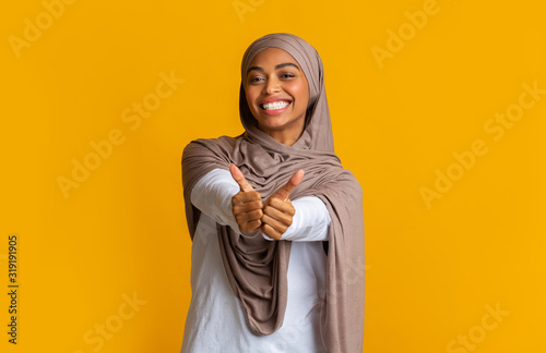 Positive afro muslim girl in hijab gesturing thumbs up Wallpaper Mural