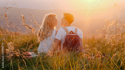 Valokuvatapetti Loving couple sitting on a mountain meadow and enjoys the view of the sunset