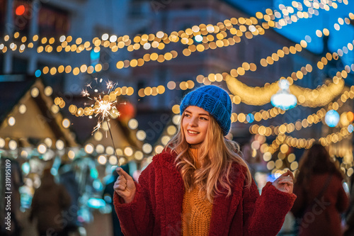 Fotografie, Obraz Outdoor night portrait of happy smiling girl holding sparkler, posing at street festive Christmas fair in European city