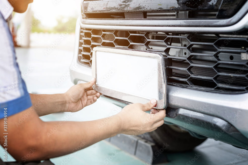 Fototapeta Technician changing car plate number in service center