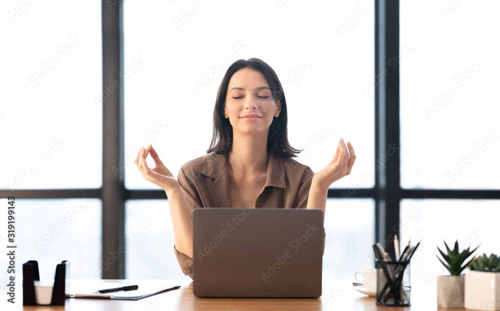 Fototapeta Girl meditating in office coping with stress