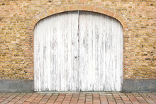 Old Wooden Gate In A Brick Wall Painted With White Paint