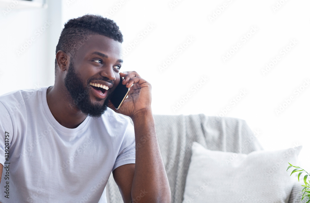 Fototapeta Talkative african american man talking on phone with friends