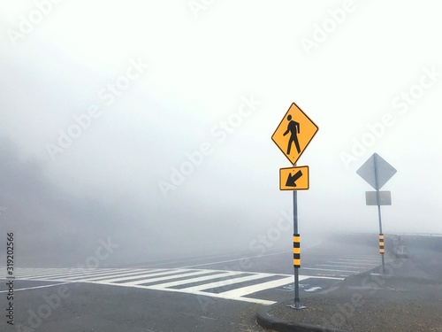Fotografie, Obraz Road Sign Against Clear Sky During Foggy Weather
