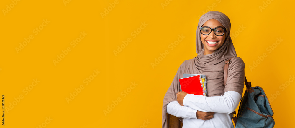 Fototapeta Portrait of black girl student in headscarf with backpack and notepads