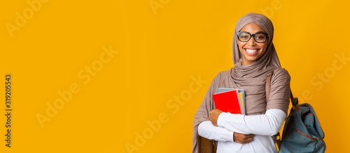 Obraz Portrait of black girl student in headscarf with backpack and notepads - fototapety do salonu