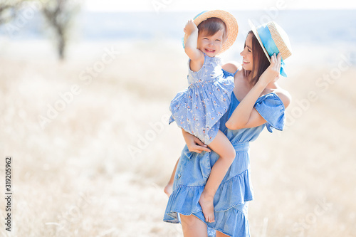 Young attractive mother and her little cute daughter having fun outdoors Wallpaper Mural