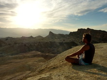 Man Sitting On Land Against Sky During Sunset