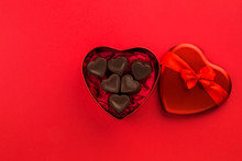Red Heart-shaped Box With Chocolate Candy On Red Background
