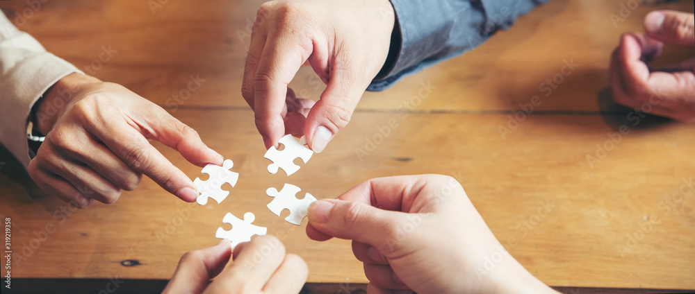 Fototapeta Collaborate with Professional Businessman and Partnership. Group of Business people holding piece of jigsaw puzzle to solution problem during brainstorming meeting -panoramic banner for web header.