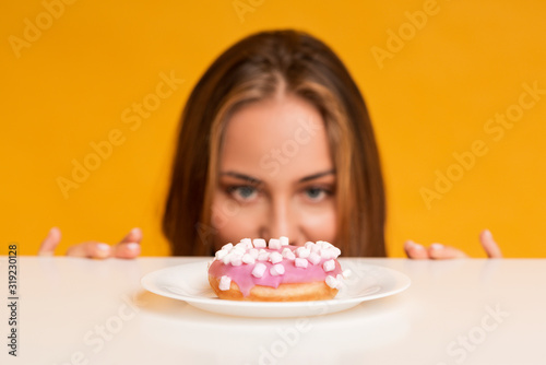 Fototapeta Hungry woman looking at donut with appetite, peeking out of table obraz