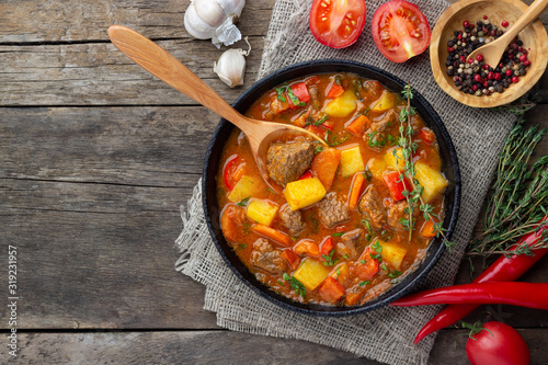 Leinwand Poster Goulash, beef stew or bogrash soup with meat, vegetables and spices in cast iron pan on wooden table