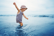 Three Years Old Boy Playing At The Beach In The Water