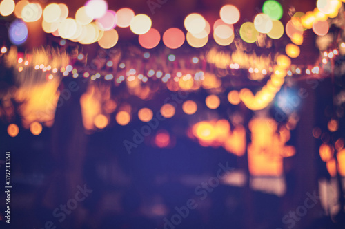Obraz blurred bokeh light on sunset with yellow string lights decor in beach resort - fototapety do salonu
