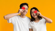 Happy asian couple covering one eye with valentine cards