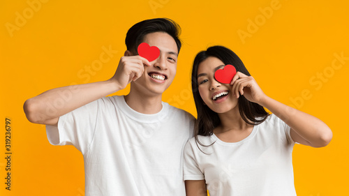 Happy asian couple covering one eye with valentine cards Canvas Print