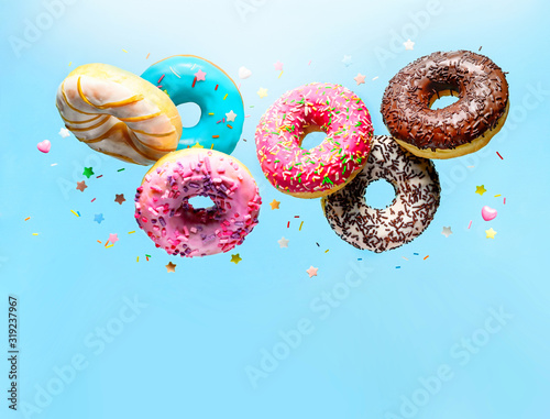 Photo Flying delicious donuts with sprinkel on blue background with copy space