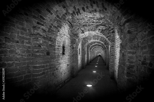 Brick tunnel archway made of red bricks as a passage between the two wings of a medieval castle. Granite stone an brick built Interior corridor way to bastions