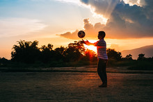 Silhouette Action Sport Outdoors Of Kids Having Fun Playing Soccer Football For Exercise In Community Rural Area Under The Twilight Sunset. Picture With Copy Space.