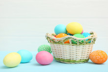 Easter Eggs In A Basket And Flowers On The Table. Festive Easter Background With Place To Insert Text.