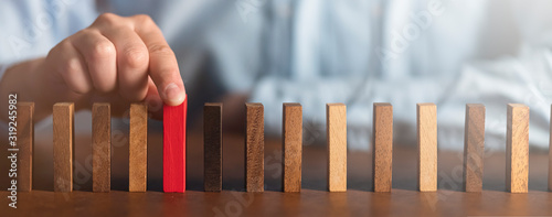 Fototapeta business man try choose red wood block on wooden table and dark background business organization startup concept obraz