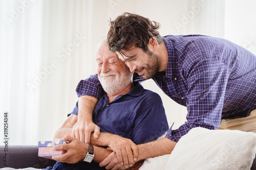 Obraz young man hugs the uncle old man warmly inside the house, son happy and love his father or grand father with gift box concept - fototapety do salonu