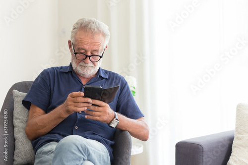 elder gray beard white hair with glasses looking attention at his smartphone to reading news at home alone Wallpaper Mural