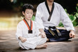 Fighter kid in Taekwondo uniform sitting concentration for training self defense body and mild.