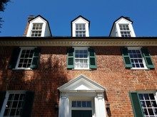 Red Brick House With Windows And Green Shutters