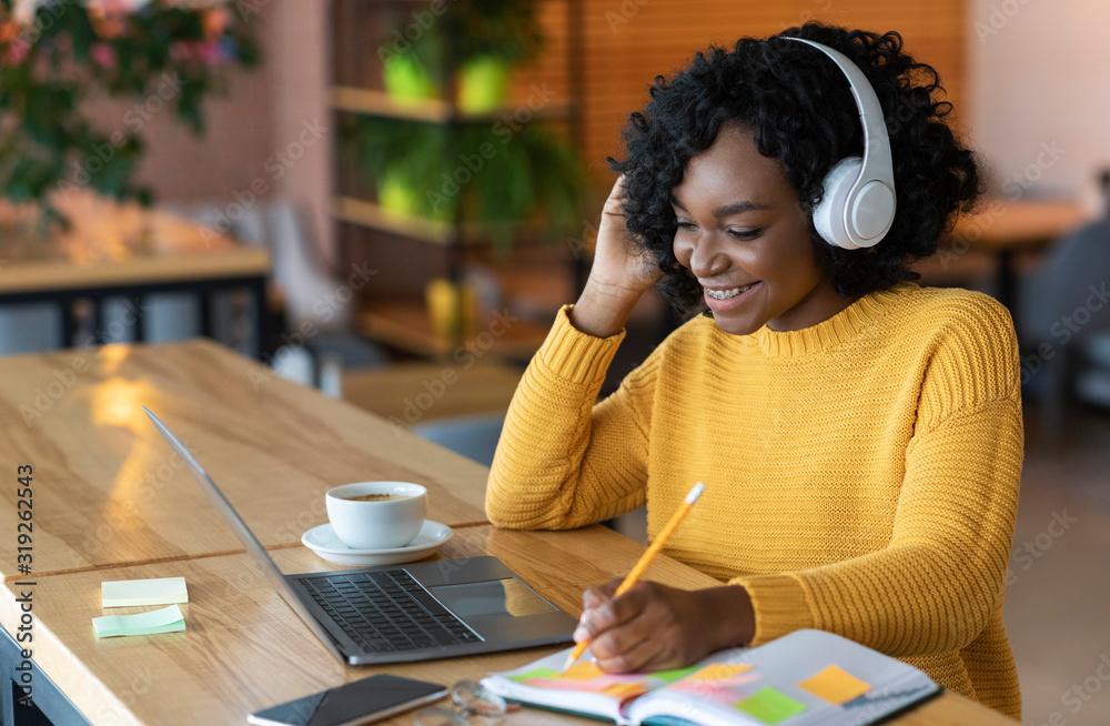 Fototapeta Smiling african girl in headphones looking at laptop, cafe interior