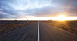 Panoramic landscape of empty highway country road in iceland, rural area desert lava moonscape with sunset sunrise in background. driving freedom adventure feeling.