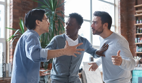 Canvas-taulu Multiracial coworkers having quarrel in office, conflict of interest