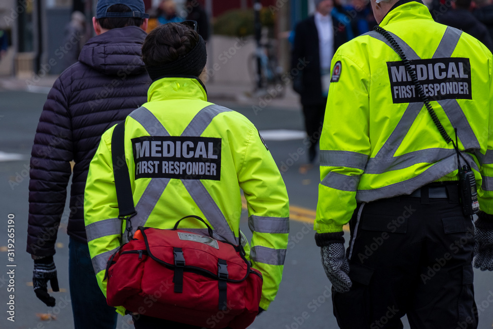 Fototapeta St. John's, Newfoundland/Canada-January 2020:Medical first responders walking along a road wearing black wool stocking caps, yellow reflective coats with medical first responder in grey letters.
