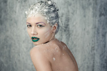 Portrait Women With Creative Makeup With Green Lips In Studio On Gray Background