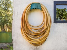 Long Weathered Garden Hose Hanging On A White Wall During Daytime