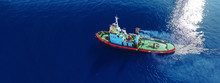 Aerial Drone Ultra Wide Photo Of Assisting Tug Boat Cruising In Mediterranean Logistics Port With Deep Blue Sea