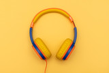 Multi-colored kids headphones on yellow pastel background. Minimalistic fashion music concept. Top view, flat lay, copy space