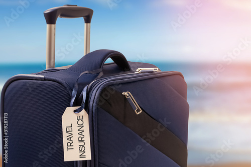 Photo Suitcase with TRAVEL INSURANCE label, closeup