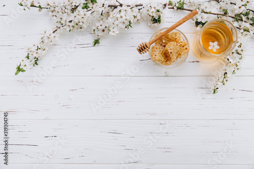 Obraz Spring composition. A cup of herbal tea and a jar of honey on a white wooden background, cherry flowers top view. Place for text. Healthy food concept. - fototapety do salonu
