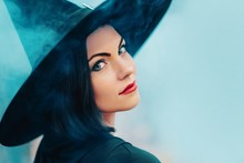Portrait Of Woman As Witch In Black On Blue Fog, Smoke Background. Fairy Tale Concept, Halloween, Cosplay.