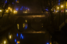 Utrecht, Netherlands, January 21st, 2020. Double Arc Stone Bridge Across Canal In The Center Of Utrecht. Misty Evening, Night View Of Canal, Old Dutch Houses, Bicycles Along The Canal.