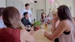 Friends giving birthday gift to woman at restaurant table