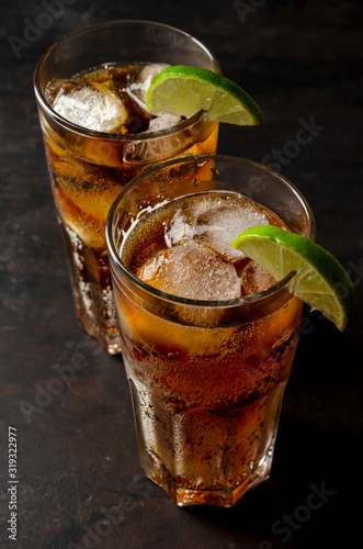 soda or cocktail with ice on table against black background
