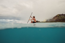 Young Man Paddle Boards Around...