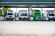 canvas print picture - Different big rigs semi trucks with semi trailers standing on the fuel station for refueling for continue the cargo delivery route