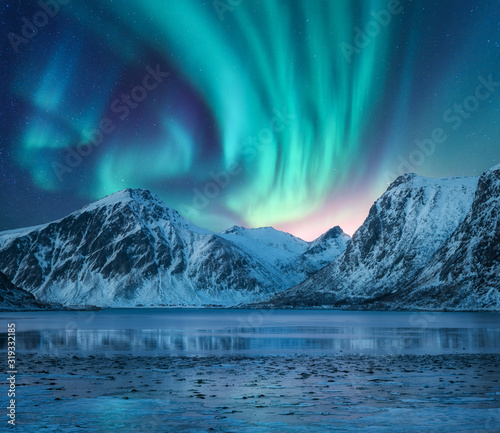 Aurora borealis over the snowy mountains, coast of the lake and reflection in water фототапет