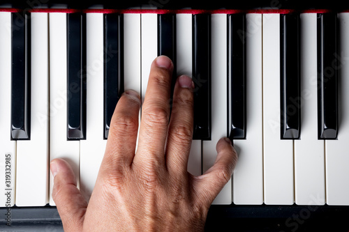 right hand playing a A Minor inversion chord on the piano Wallpaper Mural
