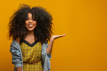 Cheerful Afro Woman Points Away On Copy Space, Discusses Amazing Promo, Gives Way Or Direction, Wears Yellow Warm Sweater, Has Pleasant Smile, Feels Optimistic, Isolated Over Yellow Background.