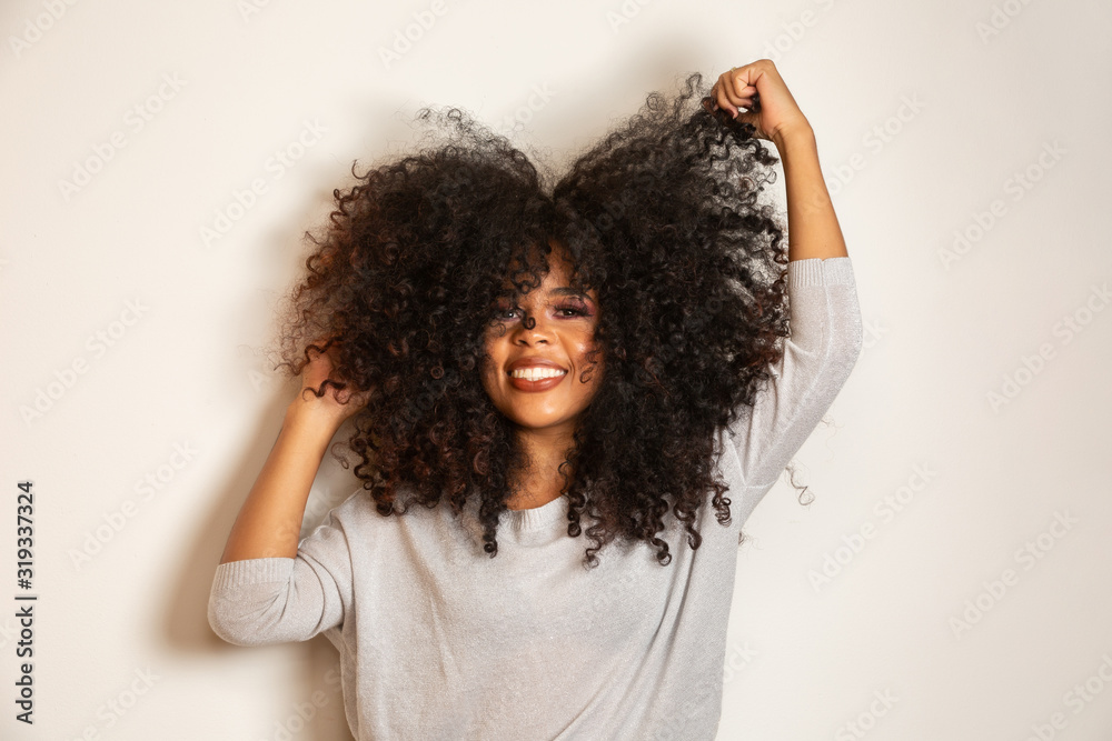 Fototapeta Beauty portrait of african american woman with afro hairstyle and glamour makeup. Brazilian woman. Mixed race. Curly hair. Hair style. White background.