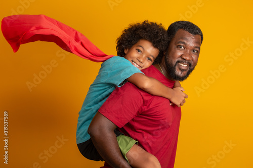 Obraz African Father and Son playing Superhero at the day time. People having fun yellow background. Concept of friendly family. - fototapety do salonu